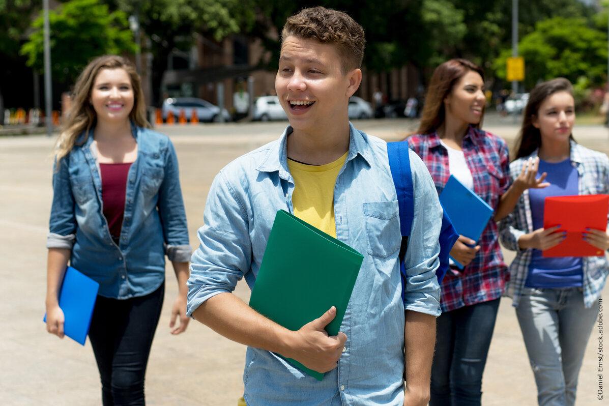 Ein junger Mann auf der Straße, dahinter drei junge Frauen. Alle tragen Schreibmappen unter dem Arm.