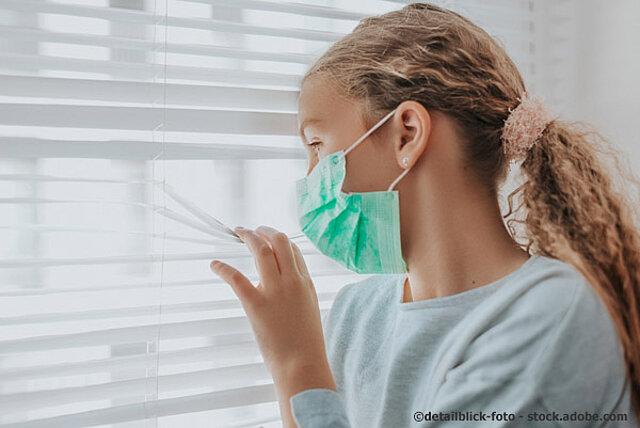 Ein junge Frau mit Mund- und Nasenschutz sieht durch eine Fenster-Jalousie nach draussen.